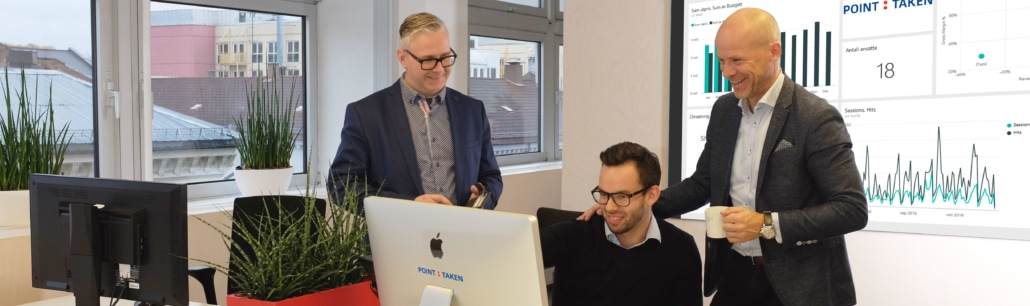 Three men looking at a picture with analytics in the background.
